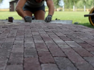 man-on-his-knees-paving-brick-floorings-in-the-gar-ZFWYKTS